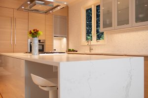 Custom home builder in Montclair, modern kitchen shown in tan and white with vase of flowers on countertop