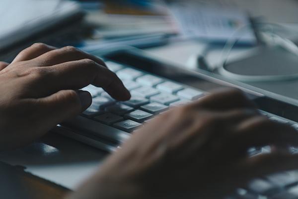 Website designer Ocean County at work, hands shown on keyboard